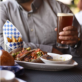 Man holding glass of beer with plate of seafood tacos and fries
